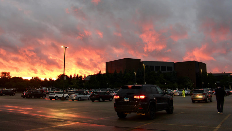 The sun sets during a drive-in prayer vigil for Black lives in the parking lot of Willow Creek Community Church's main campus in South Barrington, Illinois, Wednesday, June 10, 2020. RNS photo by Emily McFarlan Miller