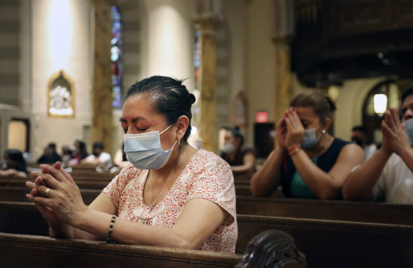 Claudia Balderas, 51, prays for her brother, who died from COVID-19 in May, on July 7, 2020, while attending the first in-person Mass in almost four months at St. Bartholomew Roman Catholic Church in the Queens borough of New York. (AP Photo/Jessie Wardarski)