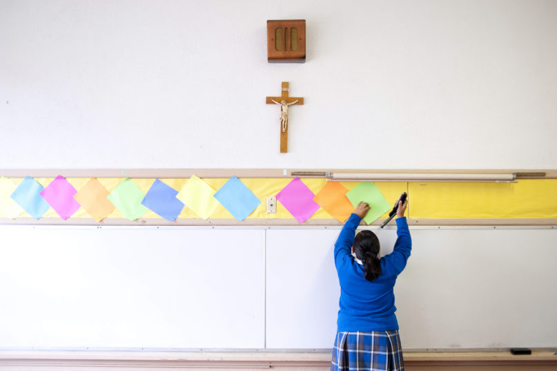 FILE - This July 18, 2012 file photo shows a student stapling colored paper to the wall of a classroom after summer school at Our Lady of Lourdes in Los Angeles. (AP Photo/Grant Hindsley)