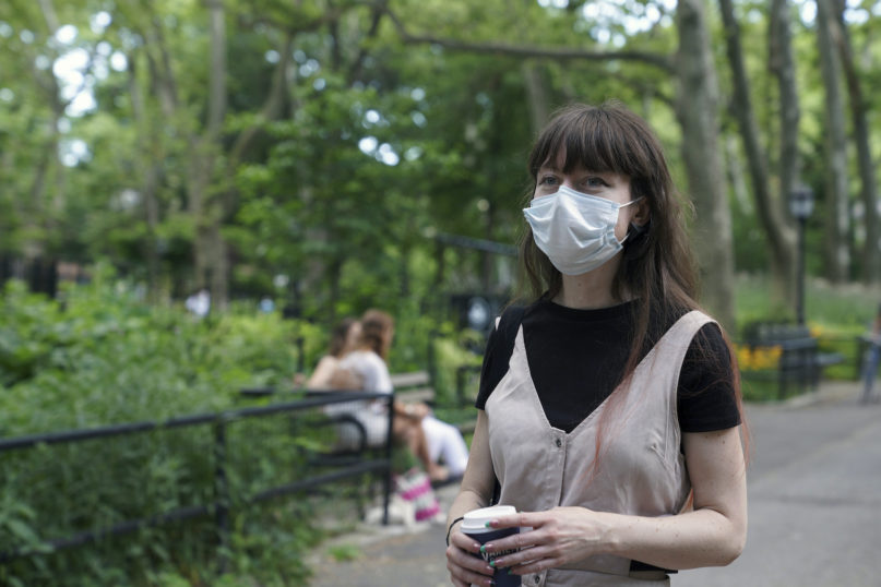 """In this June 22, 2020 photo, Marissa Oliver, a COVID-19 survivor who found comfort discussing her experience with the virus and fear of death at Death Cafe meetups, walks through a park in her neighborhood in the Brooklyn borough of New York. Others attending virtual Death Cafes, part of a broader """"death-positive"""" movement to encourage more open discussion about grief, trauma and loss, are coping with deaths from COVID-19, cancer and other illnesses. (AP Photo/Emily Leshner)"""