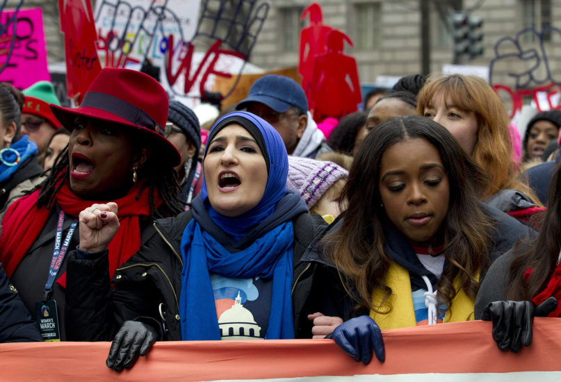 Organizers of the 2019 Women's March, Linda Sarsour, center, and Tamika Mallory, right, join other demonstrators on Pennsylvania Avenue during the Women's March in Washington on Saturday, Jan. 19, 2019. (AP Photo/Jose Luis Magana)