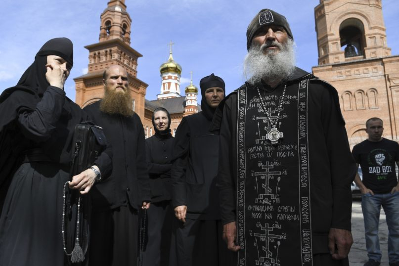 In this file photo taken on June 17, 2020, Father Sergiy, right, a Russian monk who has defied the Russian Orthodox Church's leadership, speaks to journalists in Sredneuralsk, Russia. The Russian Orthodox Church on July 3, 2020, defrocked Father Sergiy, who has defied the coronavirus lockdown orders and has taken control over a monastery. (AP Photo/Vladimir Podoksyonov, FILE)