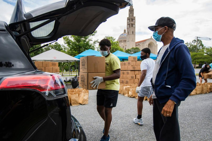 Volunteers Leonard Gresham, 17, left, and his brother Joshua Gresham, 14, back center, from Bowie, Maryland, load food items into a car during an event to provide for families affected by the coronavirus pandemic at the Basilica of the National Shrine of the Immaculate Conception, Friday, July 10, 2020, in Washington. The food distribution was hosted by the Catholic Charities of the Archdiocese of Washington. (AP Photo/Manuel Balce Ceneta)