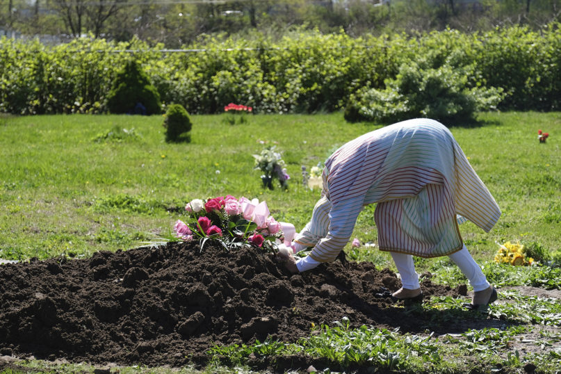 Erika Bermudez becomes emotional as she leans over the grave of her mother, Eudiana Smith, after she was buried in Bayview Cemetery, Saturday, May 2, 2020, in Jersey City, New Jersey. Bermudez was not allowed to approach the gravesite until after cemetery workers had buried her mother completely. Other members of the family and friends stayed in their cars. (AP Photo/Seth Wenig)
