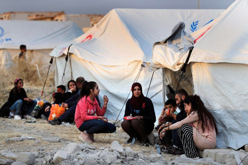 Syrians displaced by the Turkish military operation in northeastern Syria wait to receive tents and aid supplies at the Bardarash refugee camp, north of Mosul, Iraq, on Oct. 17, 2019. (AP Photo/Hussein Malla)