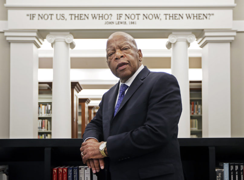 In this Nov. 18, 2016, file photo, U.S. Rep. John Lewis, D-Ga., poses for a photograph under a quote of his that is displayed in the Civil Rights Room in the Nashville Public Library in Nashville, Tennessee. (AP Photo/Mark Humphrey, File)