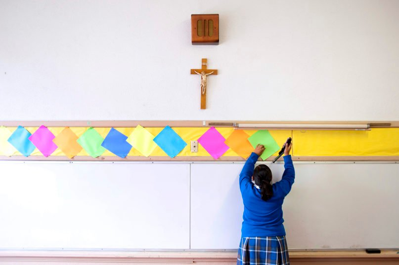 This July 18, 2012, file photo shows a student stapling colored paper to the wall of a classroom after summer school at Our Lady of Lourdes in Los Angeles. (AP Photo/Grant Hindsley)