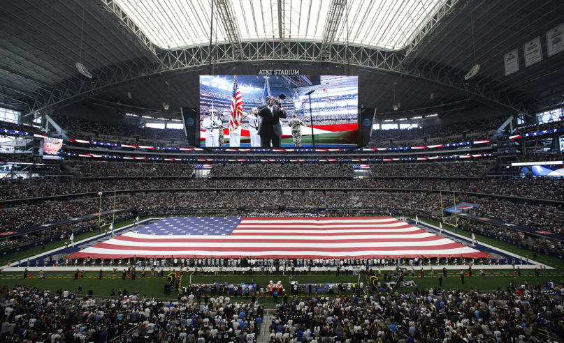 A field-sized U.S. flag is unfurled during the playing of the national anthem inside AT&T Stadium before a NFL football game between the New York Giants and Dallas Cowboys in Arlington, Texas, on Sept. 8, 2019. (AP Photo/Roger Steinman)