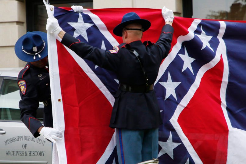 """A Mississippi Highway Safety Patrol honor guard folds the retired Mississippi state flag after it was raised over the Capitol grounds one final time in Jackson, Mississippi, on July 1, 2020. The banner was the last state flag with the Confederate battle emblem on it. A condition on the retirement is that the next state flag include the phrase """"In God We Trust."""" (AP Photo/Rogelio V. Solis)"""