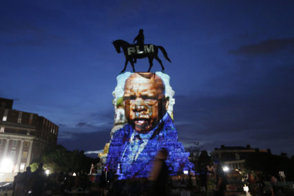 An image of the late Georgia Congressman and civil rights pioneer U.S. Rep. John Lewis is projected on to the pedestal of the statue of confederate Gen. Robert E. Lee on Monument Avenue, Wednesday, July 22, 2020, in Richmond, Va. The statue has become a focal point for the Black Lives Matter protests in the area. (AP Photo/Steve Helber)