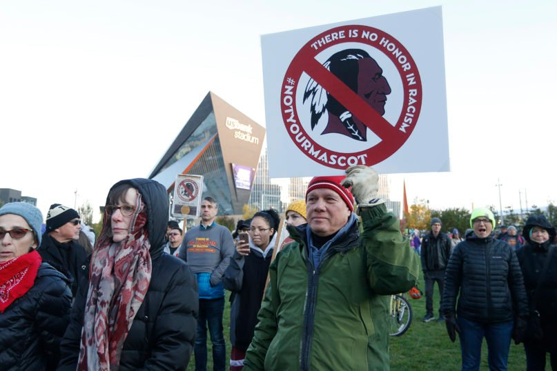 In this Oct. 24, 2019, file photo, people protest against the Redskins team name outside U.S. Bank Stadium before an NFL football game between Minnesota and Washington in Minneapolis. A new name must still be selected for the Washington football team, one of the oldest and most storied teams in the National Football League, and it is unclear how soon that will happen. But for now, arguably the most polarizing name in North American professional sports is gone at a time of reckoning over racial injustice, iconography and racism in the U.S.  (AP Photo/Bruce Kluckhohn, File)
