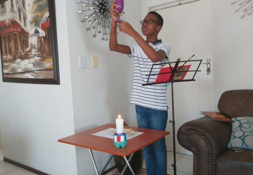 Sandile Manyike, 15, raises a chalice as he reenacts the liturgy on the third Sunday of the Easter season, while Masses were cancelled due to the coronavirus, in South Africa. Photo courtesy of Sandile Manyike