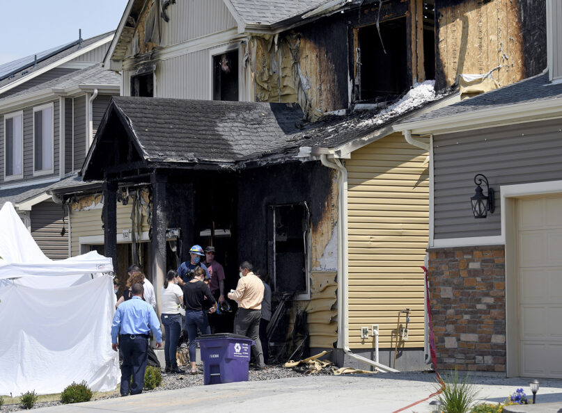 Investigators stand outside a house where five people were found dead after a fire in suburban Denver, Wednesday, Aug. 5, 2020. Three people escaped the fire by jumping from the home's second floor. The victims were a toddler, an older child and three adults. Authorities suspect the fire was intentionally set. (AP Photo/Thomas Peipert)