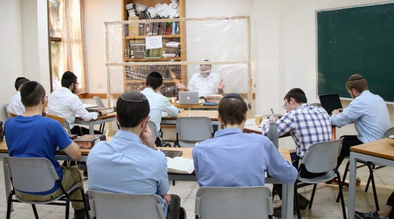 An instructor teaches from behind a partition at the Kerem B'Yavneh yeshiva, south of Tel Aviv, where gap year students are required to study in small group capsules.  Photo courtesy of Kerem B'Yavneh