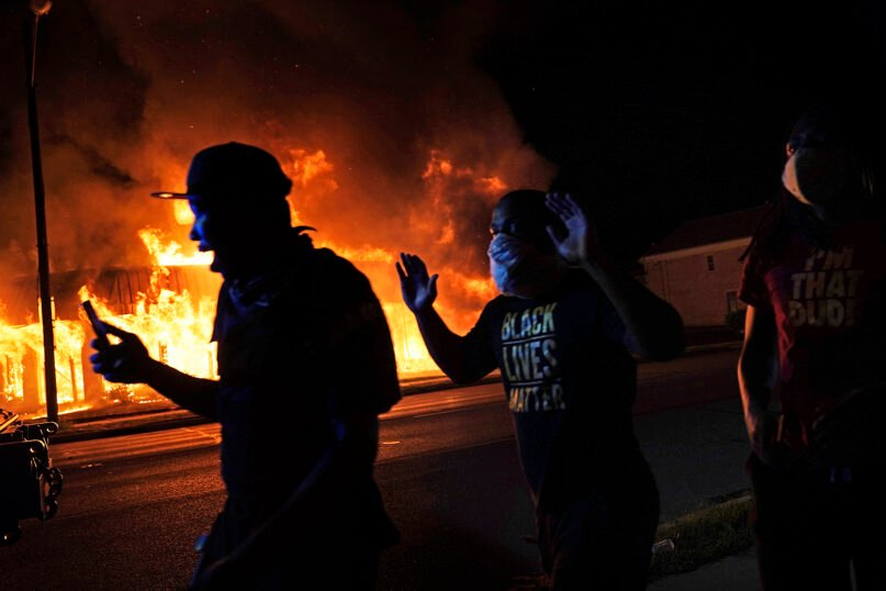 Protesters walk past police with their arms up, late Monday, Aug. 24, 2020, in Kenosha, Wisconsin, as a building burns in the background. Protests erupted following the police shooting of Jacob Blake. (AP Photo/David Goldman)