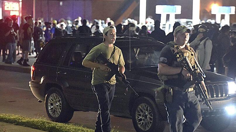 Kyle Rittenhouse, left, walks along Sheridan Road in Kenosha, Wisconsin, Tuesday, Aug. 25, 2020, with another armed civilian. (Adam Rogan/The Journal Times via AP)