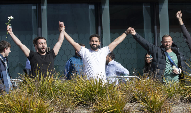 Mosque shooting survivors from left, Mustafa Boztas, Wassail Daragmih and Temel Atacocugu celebrate as they leave the Christchurch High Court after the sentencing hearing for Australian Brenton Harrison Tarrant, in Christchurch, New Zealand, on Aug. 27, 2020. Tarrant, a white supremacist who killed 51 worshippers at two New Zealand mosques in March 2019, was sentenced to life in prison without the possibility of parole. (AP Photo/Mark Baker)
