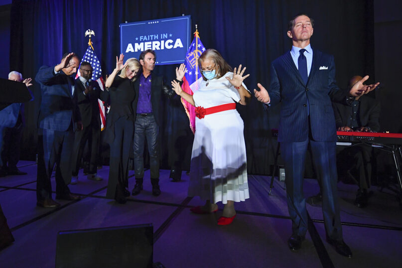 """In this July 23, 2020, file photo, from right, Faith & Freedom Coalition founder Ralph Reed, Alveda King, Journey keyboardist Jonathan Cain, White House faith adviser Paula White-Cain and others pray on stage during an Evangelicals for Trump campaign event titled """"Praise, Prayer and Patriotism"""" in Alpharetta, Georgia. President Donald Trump's reelection campaign is courting religious voters in part by seeking to portray Democrats as a threat to religious freedom — a pitch amplified by disputes over the issue during the coronavirus pandemic. (AP Photo/John Amis, File)"""