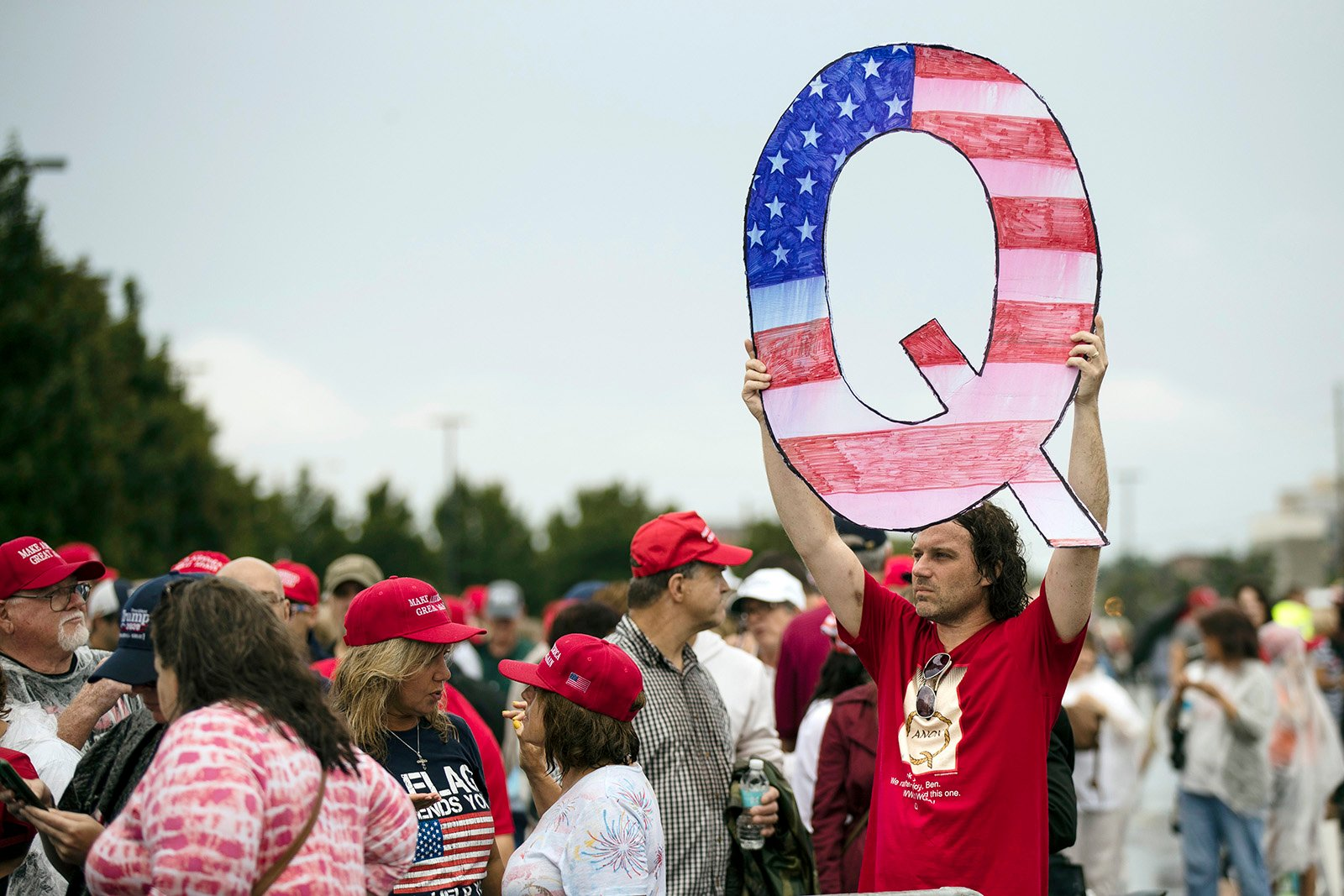 In this Aug. 2, 2018, file photo, David Reinert holds a Q sign while waiting in line with others to enter a campaign rally with President Donald Trump in Wilkes-Barre, Pennsylvania. The far-right QAnon conspiracy theory forged in a dark corner of the internet has come into the mainstream political arena. (AP Photo/Matt Rourke)