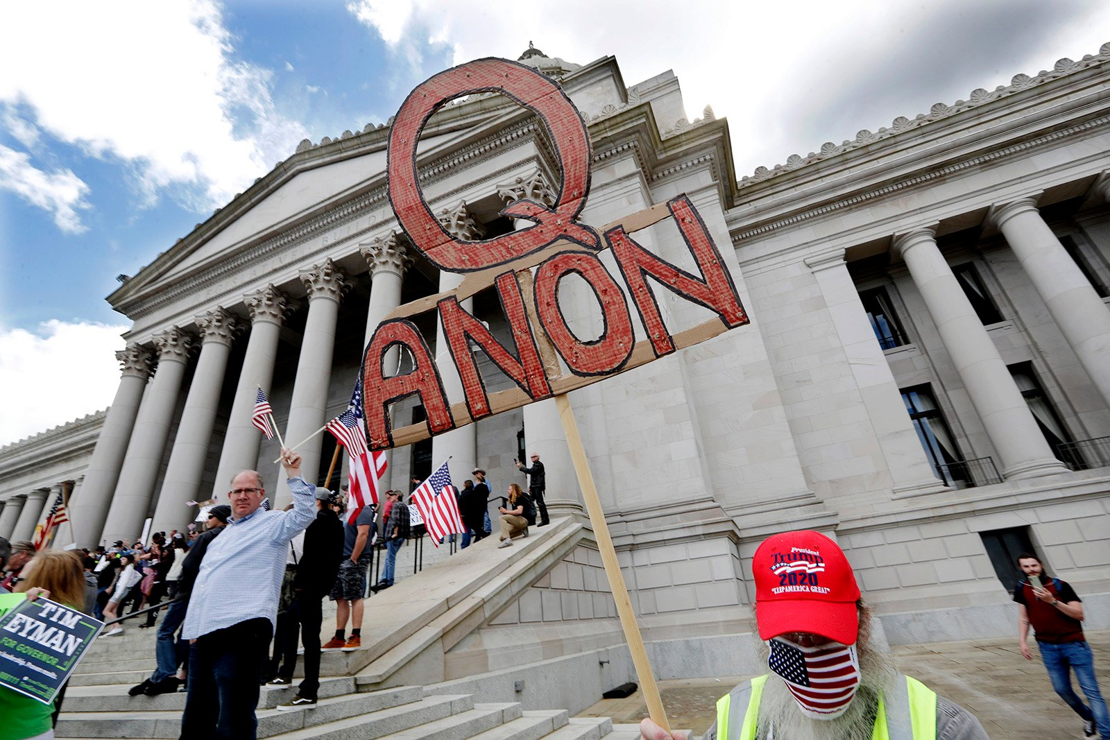 """A demonstrator holds a QAnon sign as he walks at a protest opposing Washington state's stay-at-home order to slow the coronavirus outbreak April 19, 2020, in Olympia, Washington. Washington Gov. Jay Inslee had blasted President Donald Trump's calls to """"liberate"""" parts of the country from stay-at-home and other orders designed to combat the spread of the coronavirus. Inslee said Trump was fomenting a potentially deadly """"insubordination"""" among his followers before the pandemic is contained. (AP Photo/Elaine Thompson)"""