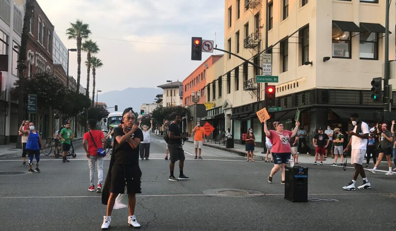 Jasmine Richards crosses her arms while addressing protesters Friday evening, Aug. 21, 2020, in Old Town Pasadena, California. RNS photo by Alejandra Molina