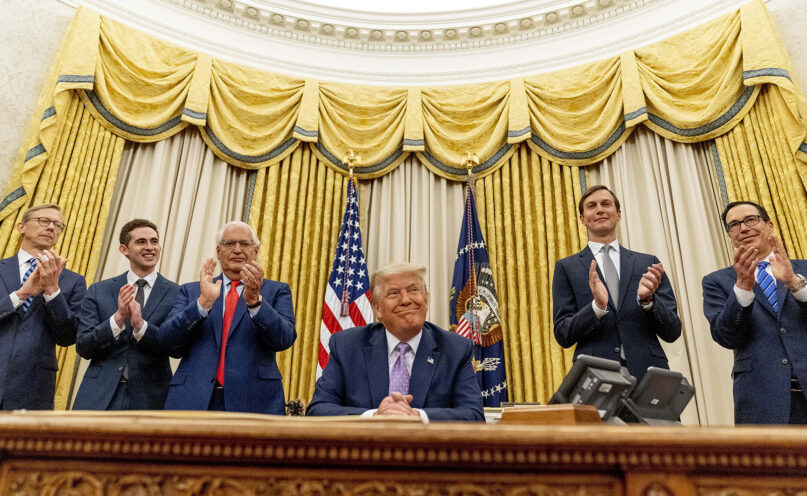 President Donald Trump, accompanied by, from left, U.S. special envoy for Iran Brian Hook; Avraham Berkowitz, assistant to the president and special representative for international negotiations; U.S. Ambassador to Israel David Friedman; President Donald Trump's White House senior adviser Jared Kushner; and Treasury Secretary Steven Mnuchin, smiles in the Oval Office at the White House on Aug. 12, 2020, in Washington. Trump said on Thursday that the United Arab Emirates and Israel have agreed to establish full diplomatic ties as part of a deal to halt the annexation of occupied land sought by the Palestinians for their future state. (AP Photo/Andrew Harnik)