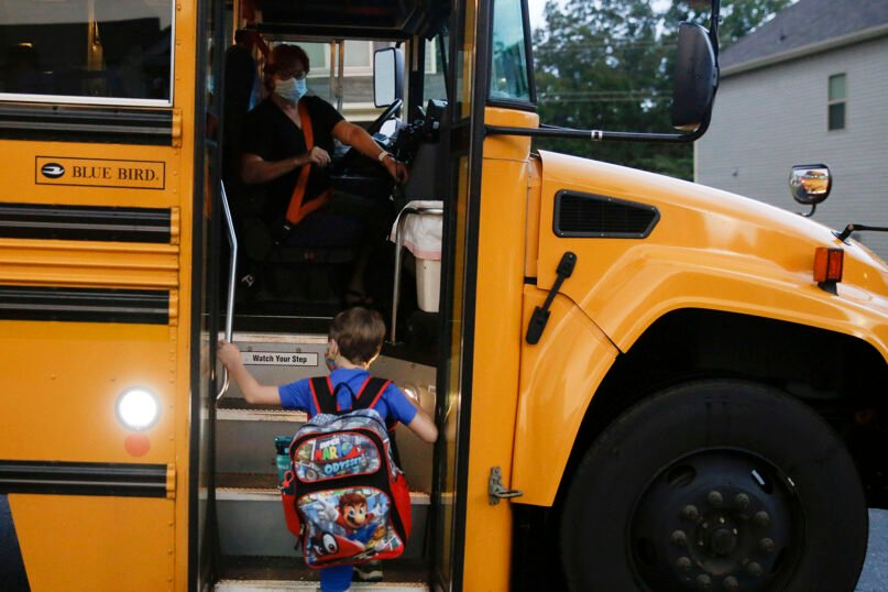 Paul Adamus, 7, climbs the stairs of a bus before the fist day of school on Monday, Aug. 3, 2020, in Dallas, Georgia. Adamus is among tens of thousands of students in Georgia and across the nation who were set to resume in-person school Monday for the first time since March. (AP Photo/Brynn Anderson)