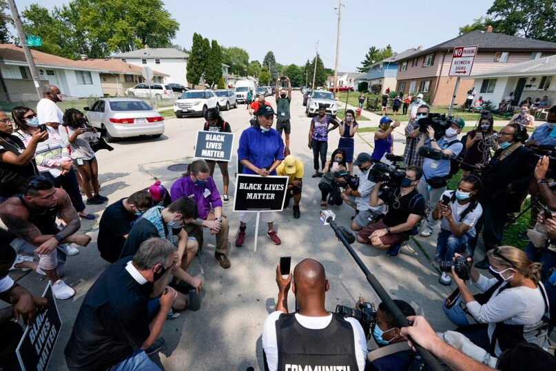 A small group of Black Lives Matter protesters pray near the site of a police shooting, Monday, Aug. 24, 2020, in Kenosha, Wisconsin. Kenosha police shot a man Sunday evening, setting off unrest in the city after a video appeared to show the officer firing several shots at close range into the man's back. (AP Photo/Morry Gash)