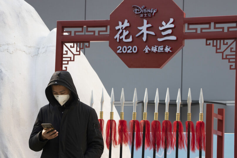 HOLD FOR STORY MULAN CHINA XINJIANG A man wearing a mask to protect from the coronavirus watch over a set promoting the Disney movie Mulan in Beijing on Wednesday, Feb. 19, 2020. Disney is under fire for partially filming its live-action reboot