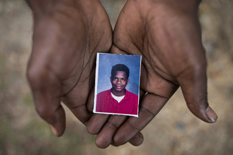 FILE - In this Monday, June 10, 2019, file photo, Joshua Love, 36, holds a photograph of himself taken at about the time he says he was sexually abused at St. Francis of Assisi School by two Franciscan friars, Brother Paul A. West and the late Brother Donald Lucas, in Greenwood, Miss. Love and his cousin La Jarvis Love have accused West, once a Franciscan friar and fourth-grade teacher, of molesting them while they were elementary-school students. West has been extradited from his home state of Wisconsin to Mississippi. (AP Photo/Wong Maye-E, File)