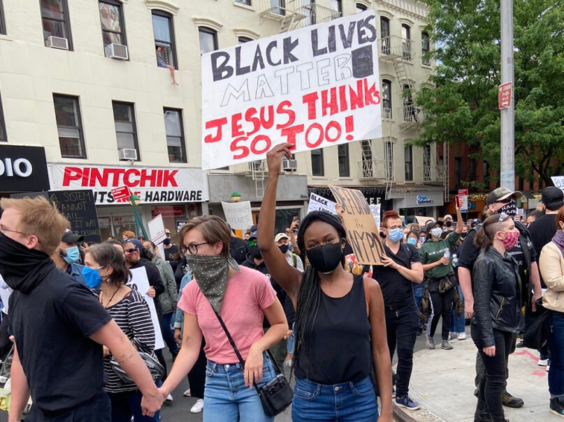 """A female demonstrator holds a sign that reads """"Black Lives Matter, Jesus Thinks So Too!"""" during a march in memory of George Floyd and against police brutality in Brooklyn, New York, Tuesday, June 2, 2020. RNS photo by Roxanne Stone"""