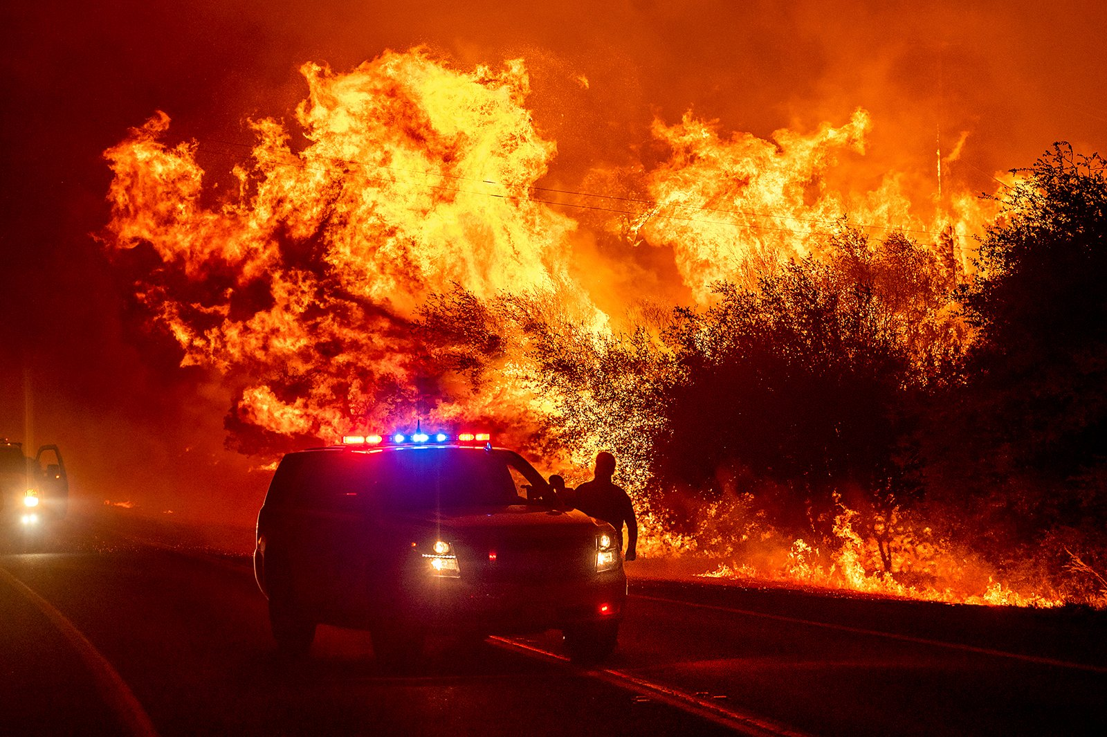 Flames lick above emergency vehicles on Highway 162 as the Bear Fire burns in Oroville, California, Wednesday, Sept. 9, 2020. The blaze, part of the lightning-sparked North Complex, expanded at a critical rate of spread as winds buffeted the region. (AP Photo/Noah Berger)