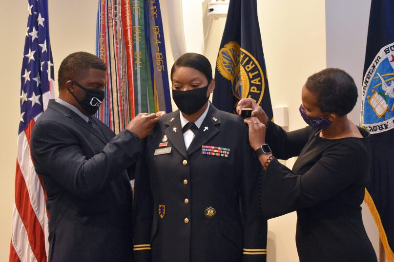 The Rev. Maurice Lawson, left, and Aretha Denard, right, change the jacket shoulder insignia for Chaplain (Col.) Monica R. Lawson, center, during her promotion ceremony to colonel on Sept. 2, 2020, at Fort Jackson, South Carolina. Photo courtesy of USACHCS