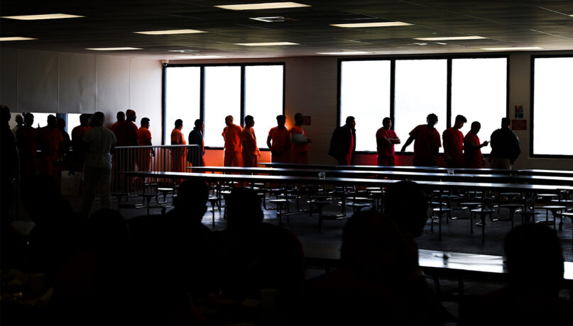 Immigration and Customs Enforcement detainees line up to be searched after lunch inside the cafeteria at the Krome Service Processing Center in Miami in November 2019. (Jack Gruber/USA Today)