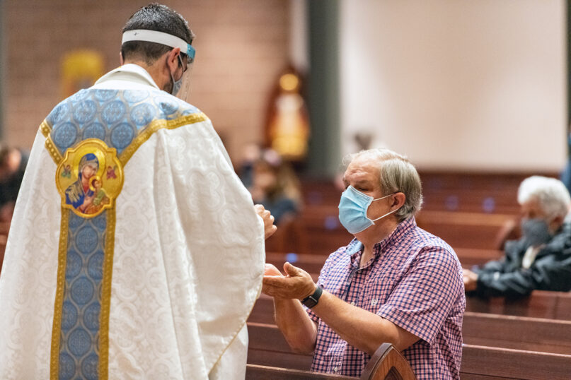Mark Galli receives Communion during Mass at St. Michael Catholic Church early Sept. 8, 2020, in Wheaton, Illinois. A priest allowed Galli to receive Communion before he was confirmed, since he was baptized a Catholic and received First Communion as a boy. RNS photo by Tom Killoran