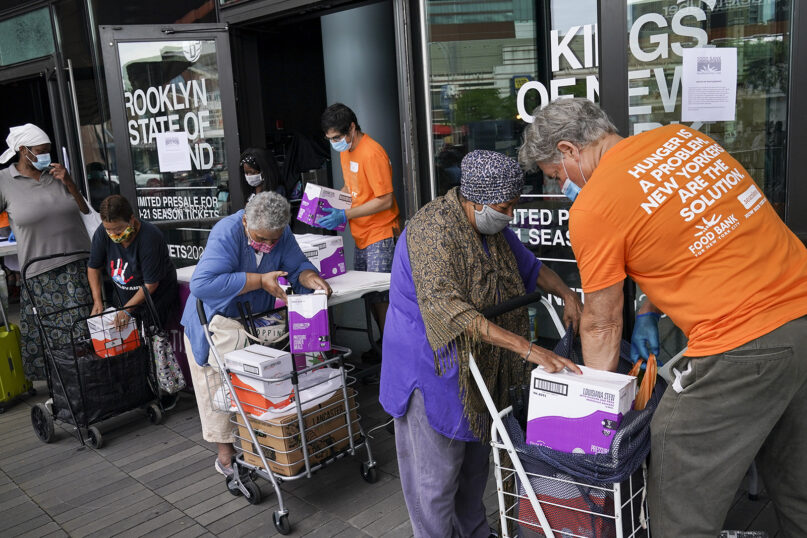 The elderly collect fresh produce and shelf-stable pantry items outside Barclays Center as Food Bank For New York City provides assistance to those in need due to the COVID-19 pandemic, Thursday, Sept. 10, 2020, in New York. (AP Photo/John Minchillo)