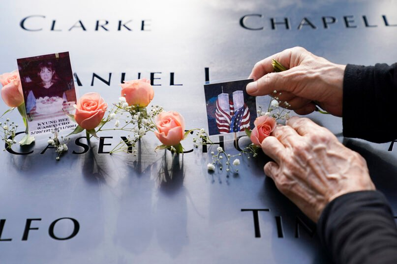 Mourners place flowers and pictures in the name cut-out of Kyung Hee (Casey) Cho at the National September 11 Memorial and Museum, Sept. 11, 2020, in New York. (AP Photo/John Minchillo)
