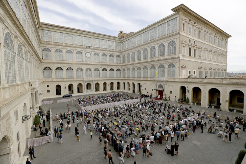 Attendees listen to Pope Francis, white figure sitting at center right, during his general audience, the first with faithful since February when the coronavirus outbreak broke out in Italy, at the San Damaso courtyard, at the Vatican, on Sept. 2, 2020. (AP Photo/Andrew Medichini)