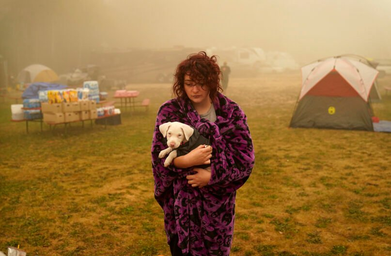 """Shayanne Summers holds her dog Toph while wrapped in a blanket after several days of staying in a tent at an evacuation center at the Milwaukie-Portland Elks Lodge, on Sept. 13, 2020, in Oak Grove, Oregon. """"It's nice enough here you could almost think of this as camping and forget everything else, almost,"""" said Summers about staying at the center after evacuating from near Molalla, Oregon, which was threatened by the Riverside Fire. (AP Photo/John Locher)"""