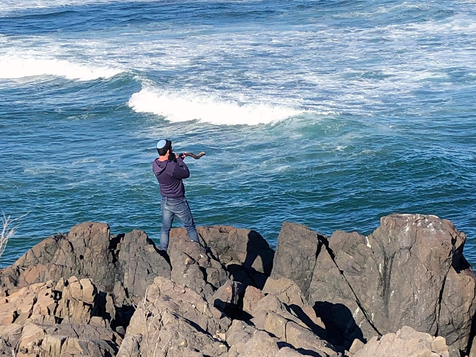 A man blows a shofar to celebrate the end of Rosh Hashanah on the Marginal Way, Sunday, Sept. 20, 2020 in Ogunquit, Maine. (AP Photo/Pat Eaton-Robb)