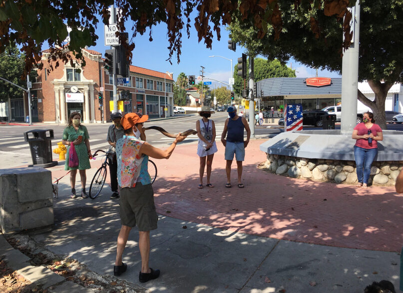 Fran Chalin blows a shofar to mark the end of Rosh Hashana, the Jewish New Year, at the intersection of Figueroa Street and York Boulevard in the Los Angeles neighborhood of Highland Park, Sunday, Sept. 20, 2020. RNS photo by Alejandra Molina