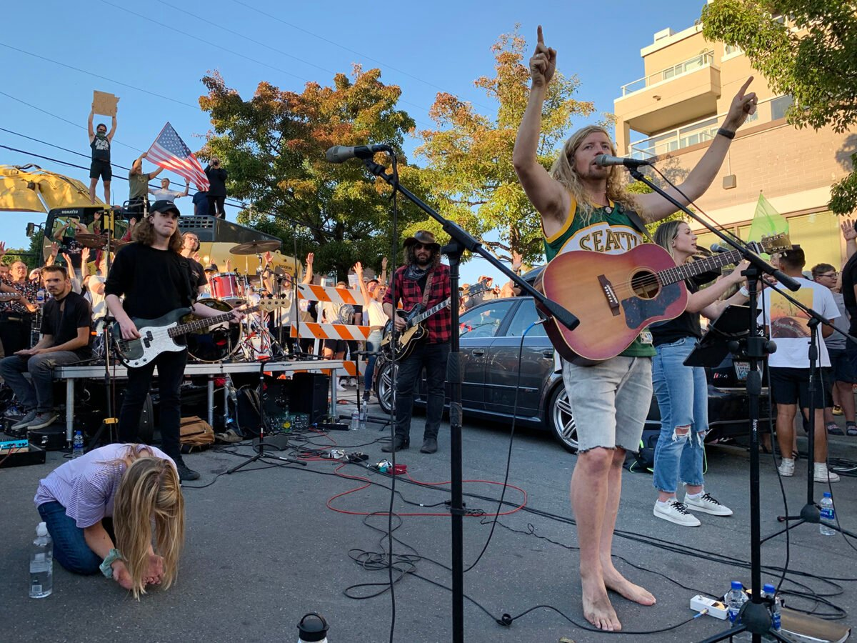 California musician Sean Feucht, right, performs with his band on a dead-end street near Seattle's Gas Works Park after the city refused him access to the park for a Labor Day concert, Sept. 7, 2020. RNS photo by Julia Duin