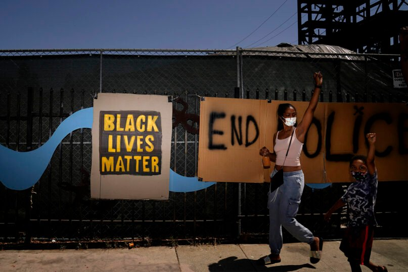 A woman and a boy raise their hands as vehicles participating in a caravan protest against racial injustice pass by them in Los Angeles on Aug. 28, 2020. (AP Photo/Jae C. Hong)
