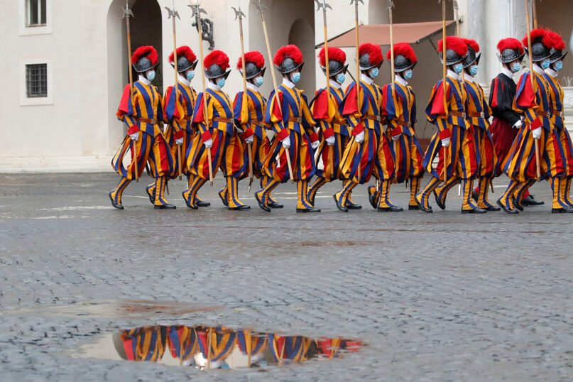 Vatican Swiss Guards wearing masks to curb the spread of COVID-19 march as they leave the St. Damaso courtyard Oct. 24, 2020, after the visit of Spain's Prime Minister Pedro Sanchez to Pope Francis at the Vatican. (AP Photo/Alessandra Tarantino)