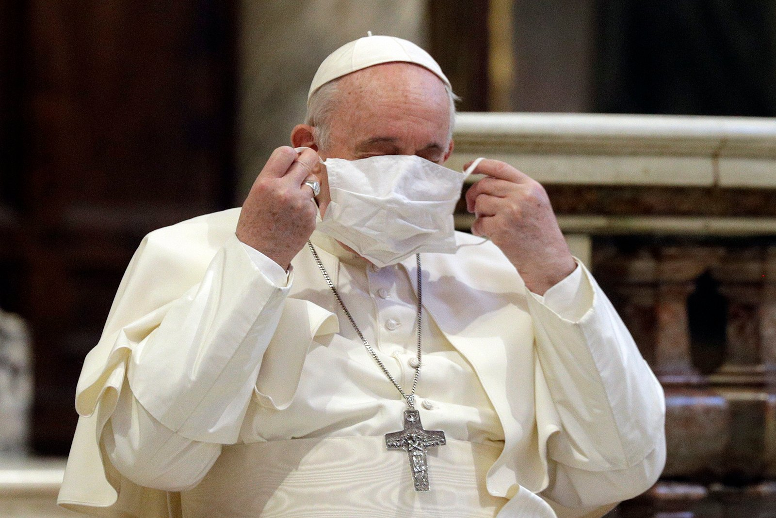 In this Tuesday, Oct. 20, 2020 file photo, Pope Francis puts on his face mask as he attends an inter-religious ceremony for peace in the Basilica of Santa Maria in Aracoeli, in Rome. Pope Francis' decision to forego wearing a face mask has been noticed, with concern, by the commission of Vatican experts he appointed to help chart the Catholic Church's path through the coronavirus pandemic and the aftermath. The Rev. Augusto Zampini, one of the key members of the pope's COVID-19 commission, acknowledged Tuesday that at age 83 and with part of his lung removed, Francis would be at high risk for complications if he were to become infected with COVID-19. (AP Photo/Gregorio Borgia, File)