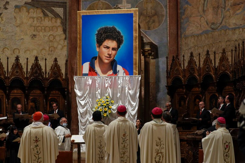 An image of 15-year-old Carlo Acutis, an Italian boy who died in 2006 of leukemia, is unveiled during his beatification ceremony, celebrated by Cardinal Agostino Vallini in the St. Francis Basilica, in Assisi, Italy, on Oct. 10, 2020. (AP Photo/Gregorio Borgia)