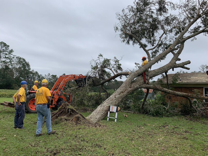 A Southern Baptist volunteer disaster relief team removes a downed tree from a home in Silverhill, Alabama, Sept. 22, 2020, following Hurricane Sally. RNS photo by Bob Smietana