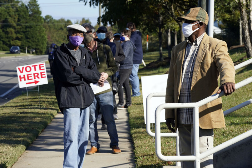 Early voters wait to cast their ballots at the South Regional Library polling location in Durham, North Carolina, Thursday, Oct. 15, 2020. (AP Photo/Gerry Broome)