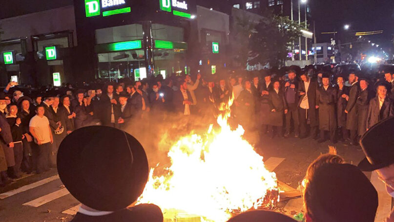 Members of the Hasidic Jewish community surround a rubbish fire in the street on Oct. 6, 2020, in the Borough Park section of New York's Brooklyn borough. Hundreds of Hasidic Jewish men gathered in the streets of Borough Park after New York Gov. Andrew Cuomo moved to reinstate restrictions on houses of worship, schools and businesses in areas where coronavirus cases are spiking. (Joe Marino/New York Post via AP)