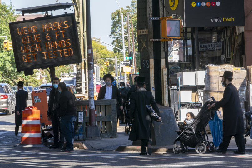 A traffic sign asks people to wear masks, wash hands, get tested and stay 6 feet apart on New Utrecht Ave. in the ultra-Orthodox Jewish neighborhood of Borough Park in the Brooklyn borough of New York, Wednesday, Oct. 14, 2020. (AP Photo/Mary Altaffer)